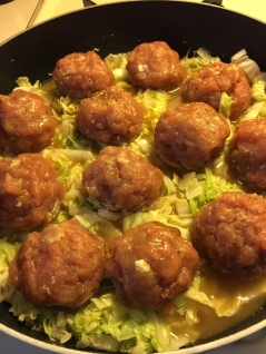 Meatballs sit on the cabbage and simmer